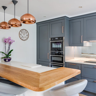 Design ideas for a large traditional u-shaped open plan kitchen in Hertfordshire with an integrated sink, shaker cabinets, grey cabinets, quartzite benchtops, metallic splashback, glass tile splashback, light hardwood floors, a peninsula and white benchtop.