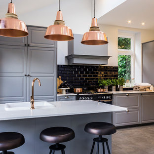 Inspiration for a large country open plan kitchen in London with raised-panel cabinets, grey cabinets, composite countertops, ceramic splashback, porcelain flooring, an island, black appliances and black splashback.