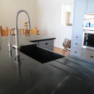 トロントのシャビーシック調のおしゃれなアイランドキッチン (アンダーカウンターシンク、シェーカースタイル扉のキャビネット、グレーのキャビネット、ソープストーンカウンター、白いキッチンパネル、ガラスタイルのキッチンパネル、シルバーの調理設備の、スレートの床) の写真