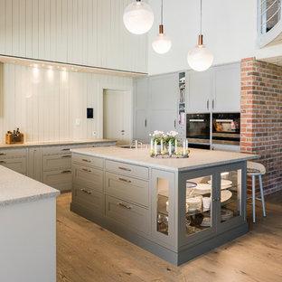 Offene Skandinavische Küche in U-Form mit Schrankfronten im Shaker-Stil, beigen Schränken, Küchenrückwand in Beige, Rückwand aus Holz, schwarzen Elektrogeräten, hellem Holzboden, Kücheninsel und beigem Boden in Sonstige