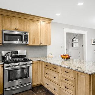 Photo of a medium sized traditional u-shaped kitchen/diner in Philadelphia with a submerged sink, shaker cabinets, light wood cabinets, granite worktops, glass tiled splashback, grey splashback, black appliances, lino flooring and a breakfast bar.