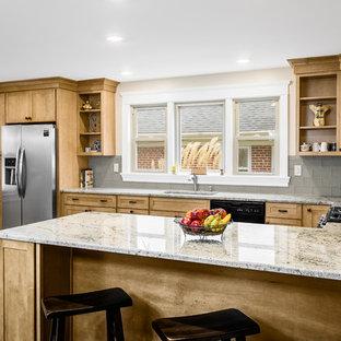 Inredning av ett amerikanskt mellanstort kök, med en undermonterad diskho, skåp i shakerstil, skåp i ljust trä, granitbänkskiva, stänkskydd i glaskakel, grått stänkskydd, svarta vitvaror, linoleumgolv och en halv köksö