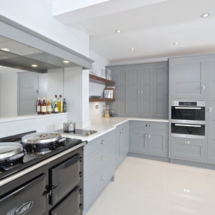 Mid-sized transitional l-shaped kitchen in Hampshire with recessed-panel cabinets, grey cabinets, limestone benchtops, mirror splashback, porcelain floors and white floor.