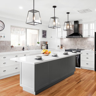 Inspiration for a large traditional l-shaped eat-in kitchen in Perth with shaker cabinets, white cabinets, black appliances, medium hardwood floors, brown floor, white benchtop, a farmhouse sink, beige splashback, with island, quartz benchtops and ceramic splashback.