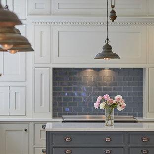 サリーの大きいヴィクトリアン調のおしゃれなキッチン (エプロンフロントシンク、シェーカースタイル扉のキャビネット、ベージュのキャビネット、人工大理石カウンター、グレーのキッチンパネル、磁器タイルのキッチンパネル、黒い調理設備、磁器タイルの床、ベージュの床、白いキッチンカウンター) の写真