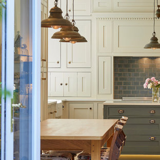 Large traditional l-shaped eat-in kitchen in Surrey with a farmhouse sink, shaker cabinets, beige cabinets, solid surface benchtops, grey splashback, porcelain splashback, black appliances, porcelain floors, with island, beige floor and white benchtop.
