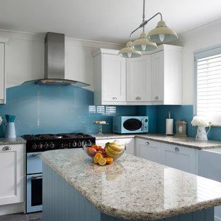 This is an example of a small classic l-shaped kitchen in Cornwall with a belfast sink, recessed-panel cabinets, white cabinets, granite worktops, blue splashback, glass sheet splashback, an island, grey floors and grey worktops.