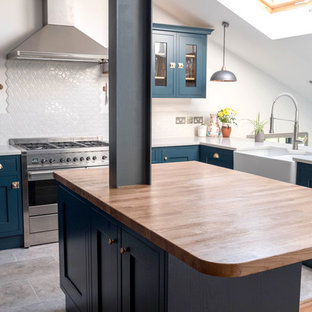 Medium sized country u-shaped open plan kitchen in London with a belfast sink, shaker cabinets, blue cabinets, white splashback, porcelain splashback, stainless steel appliances, porcelain flooring, an island, wood worktops and grey floors.