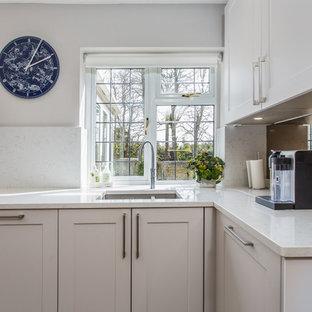 Imagen de cocina comedor minimalista con armarios estilo shaker, puertas de armario grises, encimera de cuarcita, salpicadero metalizado, salpicadero de piedra caliza, suelo de travertino y encimeras amarillas