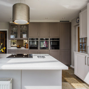 This is an example of a modern kitchen/diner in Sussex with shaker cabinets, grey cabinets, quartz worktops, metallic splashback, limestone splashback, travertine flooring and yellow worktops.