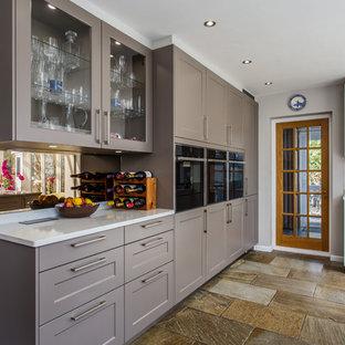 Esempio di una cucina abitabile moderna con ante in stile shaker, ante grigie, top in quarzite, paraspruzzi a effetto metallico, paraspruzzi in pietra calcarea, pavimento in travertino e top giallo