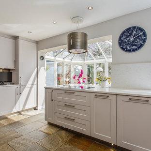 Diseño de cocina comedor minimalista con armarios estilo shaker, puertas de armario grises, encimera de cuarcita, salpicadero metalizado, salpicadero de piedra caliza, suelo de travertino y encimeras amarillas