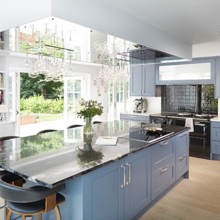 This is an example of a medium sized contemporary kitchen in Surrey with recessed-panel cabinets, blue cabinets, white splashback, a breakfast bar and beige floors.