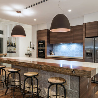 Inspiration for a contemporary galley kitchen in Sydney with flat-panel cabinets, dark wood cabinets, blue splashback, stainless steel appliances, dark hardwood floors, with island and brown floor.