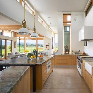デンバーの巨大なカントリー風おしゃれなキッチン (エプロンフロントシンク、フラットパネル扉のキャビネット、淡色木目調キャビネット、御影石カウンター、白いキッチンパネル、ガラス板のキッチンパネル、シルバーの調理設備、コンクリートの床、グレーの床) の写真