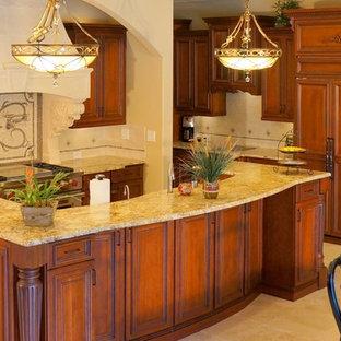 Große Klassische Wohnküche mit Doppelwaschbecken, profilierten Schrankfronten, orangefarbenen Schränken, Granit-Arbeitsplatte, Küchenrückwand in Beige, Rückwand aus Mosaikfliesen, Elektrogeräten mit Frontblende, Travertin, Kücheninsel und beigem Boden in Tampa
