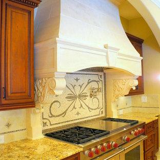 タンパの大きいトラディショナルスタイルのおしゃれなキッチン (ダブルシンク、レイズドパネル扉のキャビネット、オレンジのキャビネット、御影石カウンター、ベージュキッチンパネル、モザイクタイルのキッチンパネル、パネルと同色の調理設備、トラバーチンの床、ベージュの床) の写真