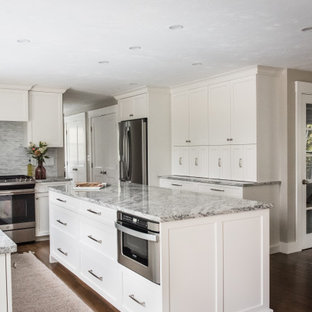 Mid-sized elegant l-shaped dark wood floor and brown floor eat-in kitchen photo in Boston with an undermount sink, shaker cabinets, white cabinets, granite countertops, gray backsplash, marble backsplash, stainless steel appliances, an island and gray countertops