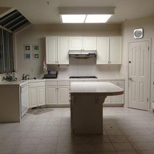 Exempel på ett stort asiatiskt kök, med en nedsänkt diskho, luckor med upphöjd panel, vita skåp, bänkskiva i kvartsit, stänkskydd i keramik, rostfria vitvaror, flera köksöar, vitt stänkskydd och klinkergolv i keramik