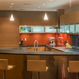 フェニックスの中くらいのモダンスタイルのおしゃれなキッチン (フラットパネル扉のキャビネット、淡色木目調キャビネット、オレンジのキッチンパネル、ガラス板のキッチンパネル、パネルと同色の調理設備、ソープストーンカウンター、コンクリートの床、茶色い床) の写真