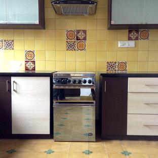Ispirazione per una cucina a L etnica con lavello a vasca singola, ante lisce, ante marroni, paraspruzzi giallo, paraspruzzi con piastrelle in ceramica, elettrodomestici in acciaio inossidabile, pavimento in terracotta e isola