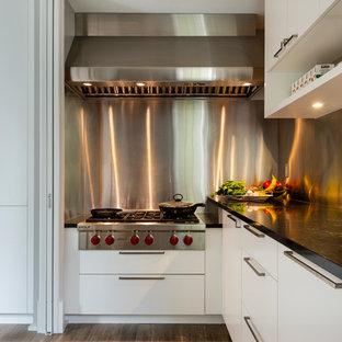 バンクーバーの広いアジアンスタイルのおしゃれなキッチン (ダブルシンク、フラットパネル扉のキャビネット、白いキャビネット、大理石カウンター、青いキッチンパネル、ガラス板のキッチンパネル、白い調理設備、淡色無垢フローリング、茶色い床、黒いキッチンカウンター) の写真
