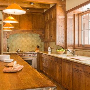 アルバカーキの広いサンタフェスタイルのおしゃれなキッチン (ドロップインシンク、シェーカースタイル扉のキャビネット、中間色木目調キャビネット、御影石カウンター、マルチカラーのキッチンパネル、セラミックタイルのキッチンパネル、シルバーの調理設備、セラミックタイルの床、ベージュの床) の写真