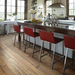 他の地域の中くらいのインダストリアルスタイルのおしゃれなキッチン (アンダーカウンターシンク、シェーカースタイル扉のキャビネット、人工大理石カウンター、白いキッチンパネル、シルバーの調理設備、クッションフロア、茶色い床、白いキャビネット) の写真