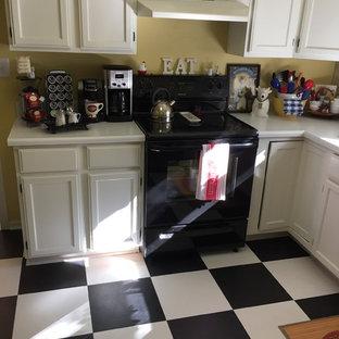 カンザスシティの中サイズのシャビーシック調のおしゃれなL型キッチン (シェーカースタイル扉のキャビネット、白いキャビネット、磁器タイルの床、人工大理石カウンター、黒い調理設備、アイランドなし) の写真