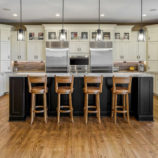 Design ideas for a traditional u-shaped kitchen in Other with an undermount sink, shaker cabinets, beige cabinets, grey splashback, matchstick tile splashback, stainless steel appliances, medium hardwood floors, with island and grey benchtop.