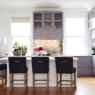 This is an example of a transitional l-shaped kitchen in Sydney with glass-front cabinets, purple cabinets, metallic splashback, metal splashback, stainless steel appliances, medium hardwood floors, with island and white benchtop.