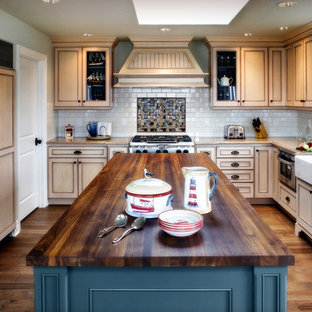 Design ideas for a mid-sized beach style u-shaped separate kitchen in Portland with a farmhouse sink, recessed-panel cabinets, beige cabinets, wood benchtops, white splashback, subway tile splashback, panelled appliances, medium hardwood floors and with island.