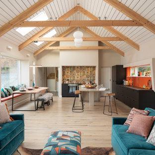 Неиссякаемый источник вдохновения для домашнего уюта: угловая кухня-гостиная среднего размера в стиле кантри с накладной раковиной, плоскими фасадами, черными фасадами, столешницей из бетона, оранжевым фартуком, техникой под мебельный фасад, светлым паркетным полом, островом, серой столешницей и балками на потолке