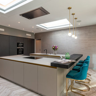 This is an example of a large contemporary u-shaped open plan kitchen in London with flat-panel cabinets, grey cabinets, ceramic flooring and multiple islands.
