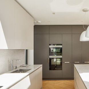 This is an example of a modern kitchen in London with a submerged sink, flat-panel cabinets, white cabinets, medium hardwood flooring, an island, brown floors and white worktops.