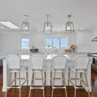 Photo of a beach style kitchen in Brisbane with a farmhouse sink, shaker cabinets, white cabinets, white splashback, stainless steel appliances, medium hardwood floors, with island and grey benchtop.