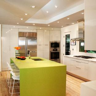 Moderne Wohnküche in U-Form mit Unterbauwaschbecken, flächenbündigen Schrankfronten, weißen Schränken, Küchengeräten aus Edelstahl, hellem Holzboden, Kücheninsel, Mineralwerkstoff-Arbeitsplatte, Küchenrückwand in Weiß und grüner Arbeitsplatte in Washington, D.C.