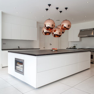 Inspiration for an expansive modern kitchen in London with flat-panel cabinets, white cabinets, stainless steel appliances and an island.