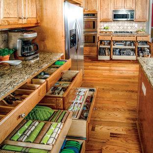 Ispirazione per una cucina ad U chic chiusa e di medie dimensioni con lavello sottopiano, top in granito, elettrodomestici in acciaio inossidabile, parquet scuro, pavimento marrone e top multicolore