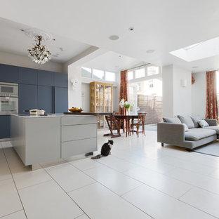 Diseño de cocina comedor en L, contemporánea, con fregadero encastrado, armarios con paneles lisos, puertas de armario azules, encimera de vidrio, electrodomésticos con paneles, suelo de baldosas de porcelana y una isla