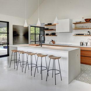 Ejemplo de cocina minimalista con armarios con paneles lisos, puertas de armario de madera oscura, una isla, suelo gris y encimeras blancas