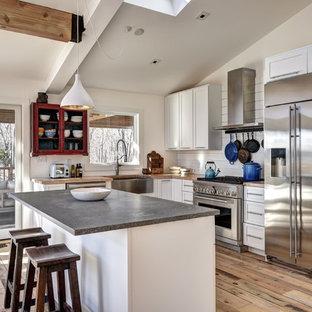 ニューヨークの中サイズのラスティックスタイルのおしゃれなキッチン (エプロンフロントシンク、シェーカースタイル扉のキャビネット、白いキャビネット、木材カウンター、白いキッチンパネル、木材のキッチンパネル、シルバーの調理設備の、淡色無垢フローリング、ベージュのキッチンカウンター、ベージュの床) の写真