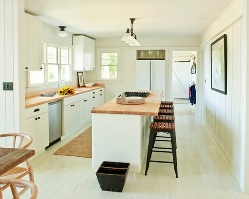 Modern Kitchen Idea In New York With White Appliances And Wood Countertops
