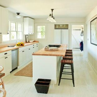 Inspiration for a modern kitchen in New York with white appliances and wood benchtops.