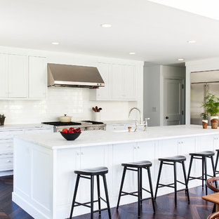 Beach style eat-in kitchen ideas - Eat-in kitchen - beach style dark wood floor and brown floor eat-in kitchen idea in Philadelphia with white cabinets, marble countertops, white backsplash, ceramic backsplash, an island, shaker cabinets and stainless steel appliances