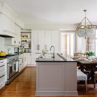 Пример оригинального дизайна: параллельная кухня в стиле современная классика с обеденным столом, белыми фасадами, столешницей из акрилового камня, серым фартуком, техникой из нержавеющей стали, паркетным полом среднего тона и островом