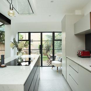 Пример оригинального дизайна: параллельная кухня в современном стиле с обеденным столом, врезной раковиной, плоскими фасадами, белыми фасадами, белым фартуком, техникой под мебельный фасад, островом, белым полом и белой столешницей