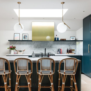 This is an example of a large transitional l-shaped kitchen in London with an integrated sink, flat-panel cabinets, blue cabinets, concrete benchtops, grey splashback, marble splashback, stainless steel appliances, cement tiles, with island and beige floor.