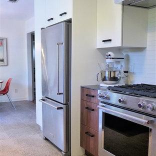 Ejemplo de cocina comedor en U, minimalista, pequeña, con fregadero de un seno, armarios con paneles lisos, puertas de armario blancas, salpicadero blanco, salpicadero de azulejos tipo metro, electrodomésticos de acero inoxidable, suelo de terrazo, península, suelo gris y encimeras grises