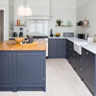 Bild på ett mellanstort vintage vit vitt l-kök, med en rustik diskho, blå skåp, marmorbänkskiva, grått stänkskydd, glaspanel som stänkskydd, svarta vitvaror, ljust trägolv, en köksö och skåp i shakerstil